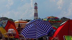 IMG_6270 Beach umbrellas and the lighthouse (Rodolfo Frino) Tags: beachumbrella beach bright color colors colour colours colorful colourful sky cloud clouds girl woman mujer lighthouse catchycolors yellow red blue green tree trees chair seat ciel cielo summertime summer