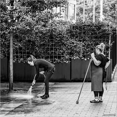 Cooperation (John Riper) Tags: johnriper street photography straatfotografie square vierkant bw black white zwartwit mono monochrome hungary budapest candid john riper fujifilm fuji xt1 18135 women suitable labour suitablelabour hose broom water cleaning cooperation waiting clogs