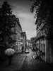 in restless dreams I walk alone (koaxial) Tags: p4173785p6ma1jpg koaxial street narrow cobblestone umbrella bregenz rainy dark grey bw schwarzweiss sky clouds himmel city stadt town perspective
