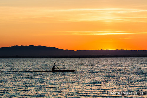 Man canoeing on sunset