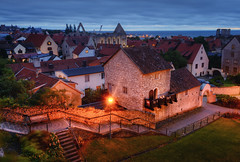Visby Town Blues (henriksundholm.com) Tags: lowaerial city urban steps medieval wall stone rock grass lawn landscape horizon dusk bluehour shadows history historical worldheritage ruin balcony architecture skyline cityscape bench railing roofs karin carin light lamp red hdr visby gotland sverige sweden