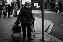 shopper (Chilanga Cement) Tags: fuji fujix100t x100t xseries x100s x100 monochrome bw blackandwhite woman lady trolley trolleys pavement sidewalk roadside road southport street streetphotography candid lightroom daylight detail