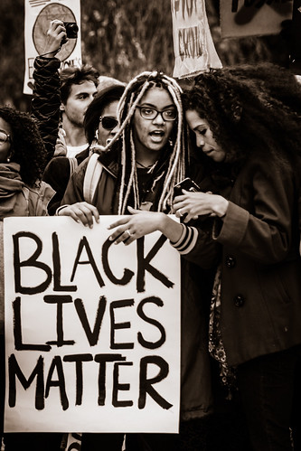 """Black women hold a sign that reads """"Black Lives Matter."""" Setting is at a rally or march."""