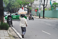 Getting ahead (Roving I) Tags: street streetvendors loads onhead danang donuts doughnuts cabs cinnamonrolls taxis traffic trees motorcycles vietnam
