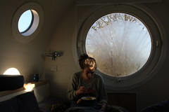 Pod Life (danieljbec) Tags: pod winchester hampshire england uk window condensation dew eating girl woman ella becker light trees porthole living space bed coffee bowl mug mango portrait portraiture