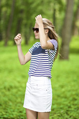 Teenagers Lifestyle Concepts. Portrait of Blond Caucasian Teenager Girl Posing Outside in Green Forest. (DmitryMorgan) Tags: 1 1319years attractive beautiful blond blondyhair casual caucasian cheerful concept cute day enjoying female forest happy holidays joyful leisure leisureactivity lifestyle lifetime lovely one outdoors park positive relaxing skirt smiling standing stripe stripy stylish summer sunglasses sunny teen teenager vacation white younggirl youth