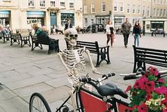 Why did the skeleton ride the bike?? (George Ffoulkes) Tags: flowers film bike bicycle 35mm skeleton nikon bath funny comedy somerset fm nikonfm2 fm2