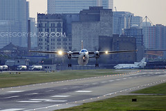 Crosswind (Greg Bajor) Tags: city uk travel england london plane airplane flying airport aircraft aviation transport flight aeroplane business commercial airline commuter docklands local klm 50 canarywharf departure propeller takeoff runway regional airliner aerospace fokker cityhopper xwind gregbajor