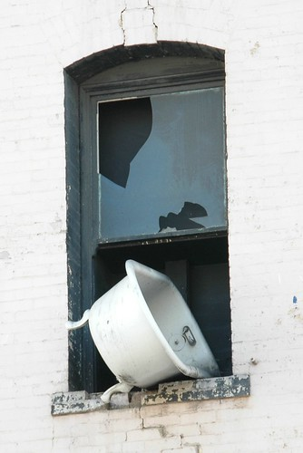 an old bath tub sticking out of an upper-level apartment window, ready to fall to the street below