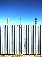 The Sky is Always Bluer (Steve Taylor (Photography)) Tags: blue shadow newzealand sky grass metal fence shiny iron dent nz barbedwire corrugated ontheothersideofthefence