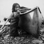 Inuit child with a canoe / Enfant inuit à côté d'un canot thumbnail