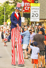Meeting Uncle Sam (wyojones) Tags: wyoming cody codystampede rodeocapitaloftheworld codystampedeparade 4thofjuly unclesam crowd spectators paradegoers boy photographer hat stilts pants redwhiteandblue hats signs wyojones