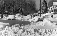 One man carries a shovel while two others shovel snow on a residential street after the snowstorm of 1982 in Denver, Colorado. (Denver Public Library Digital Collection)