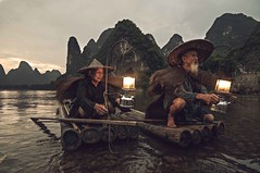 Legendary fishermen... (Syahrel Azha Hashim) Tags: singleexposure mountains tokina shallow simple dramaticsky guilin shadow touristattraction sunset conventional humaninterest handheld colorimage vacation destination china moment fishing d300s elder uwa mountain portrait lantern expression water unique holiday chinese details portraiture xingping ultrawideangle bird local traditional dof bamboo smile single detail clouds getaway nikon liriver elite beard paddle 11mm light fishermen hat scene colorful traditionalclothing cormorants iconic syahrel river birds colors bambooraft naturallight travel oldman fisherman