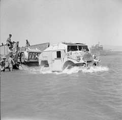 A Chevrolet FAT (Field Artillery Tractor) and 25-pdr field gun disembark from a tank landing craft during a large scale invasion exercise in the Gulf of Aqaba, 22 June 1943
