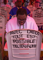 """Benin, West Africa, Ganvi, celestial church of christ men praying in front of a chair with """"with god everything is possible"""" slogan (Eric Lafforgue) Tags: africa people color church vertical religious outdoors photography community worship adult african faith religion praying christian celebration westafrica service uniforms christianity benin member 2people twopeople congregation adultsonly celestial worshiper ganvi attend colourimage     benin0262"""