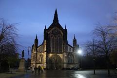 Glasgow Cathedral (elisecavicchi) Tags: trees statue dark purple cathedral dusk glasgow deep dramatic pedestrians lamplight ornate leafless wispy necropolis nightfall illuminate gloaming