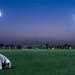 Man praying at sunset on an Aspire Zone football pitch