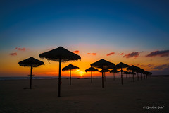Tiki sunset (grahamvphoto) Tags: outdoor sunset tiki umbrella sky beach parasole portugal algarve europe natural sun sand seascape landscape