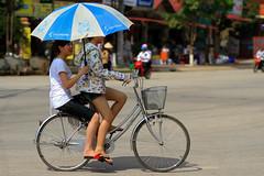 Girls on Bike Under Umbrella, Sơn La Vietnam (AdamCohn) Tags: 115kmtobnbninsnlavietnam adamcohn bnbn snla sonla sơnla vietnam bicycle bike geo:lat=21326779 geo:lon=103914251 geotagged ride ridingbike shade umbrella wwwadamcohncom thànhphốsơnla