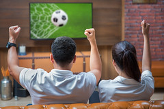 Couple having fun watching soccer game (anekphoto) Tags: family people man game green home up grass television playground sport ball fun football tv holding women focus media asia day technology play hand close control flat display euro finger background soccer watching screen off souvenir sofa entertainment human sit button change leader thumb push remote concept cheer relaxation lcd liquid channel