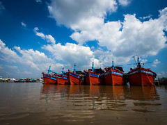 Mekong 05 (arsamie) Tags: mekong vietnam river asia boat red five blue sky clouds hot brown water muddy can tho