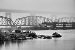 st. marys river fog (twurdemann) Tags: longexposure railroad bridge blackandwhite bw mist fog dam shoreline railway saultstemarie parkscanada waterlevel internationalbridge stmarysisland stmarysriver circa1887 canadiannationalrailway neutraldensityfilter unitedstatesborder canadaborder nd110 parkertruss circa1921 dominionbridgecompany camelbacktruss niksilverefex internationalrailroadbridge lakesuperiorcompensatingworks internationaljointcommission xf55200mm watercontroldam fujixt1