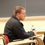 A student sitting in class while another student gives a presentation.