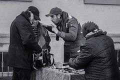 Strong Arguments (Ivan Rigamonti) Tags: bw bnw blackandwhite monochrome switzerland europe zurich urban urbanexploration street streetphotography woman man booth toycars negotiation haggling ivanrigamonti