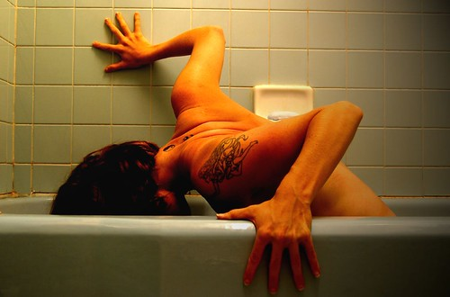 Photograph of a tattooed person with short dark hair crouched in a sea-green bathtub, arms outstretched and head in the tub. Photograph taken by J. Star and licensed under Creative Commons.