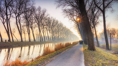 Hiking path. (rudi.verschoren) Tags: hiking path canal damme outdoor landscape landschap light trees water walkway pittoresque europe eos europa endless exposure reflection grass people colors soft glow pastel sun rays cold winter lines leaves perspective ngc long largest belgium flanders vlaanderen mist fog