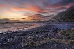 Cape Palliser Sunset (dave.fergy) Tags: ocean sunset newzealand sky lighthouse abstract building beach water composite architecture dark landscape rocks waves mood dusk stones nz wellington capepalliser on1pics