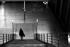 At the bottom of the staircase (pascalcolin1) Tags: paris13 bnf escalier staircase femme woman photoderue streetview urbanarte noiretblanc blackandwhite photopascalcolin lumière light ombres shadow