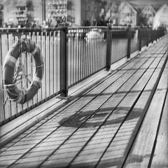 Jagged On The Jetty (cazphoto.co.uk) Tags: slr film monochrome mono shadows lifebelt jetty quay vintagecamera railings planks singlelensreflex wivenhoe ilforddelta100 120rollfilm agilux agiflex agiluxanastigmat80mmf35