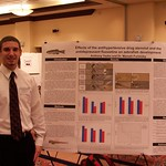 A student posing with his environmental science research poster.