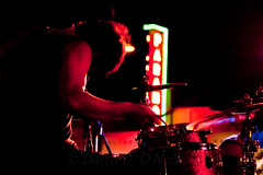 Oceans Apart 44 (LongInt57) Tags: man men person people drummer drumming drums kit night dark stage lighting theatre theater sign neon glowing red white green black concert band performing performance music kelowna bc canada okanagan motion blur cymbals