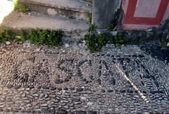 Cascata escrita com seixos pretos rolados pelo mar (Américo Meira) Tags: portugal caxias quintareal placa seixo pedra preto branco