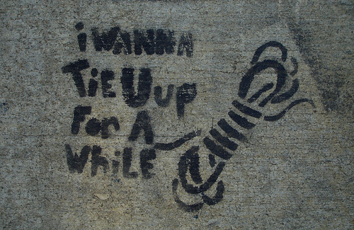 stencil graffiti: i wanna tie u up for a while (with image of a twisted coil of rope)