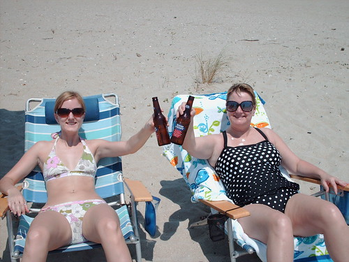 Two mature ladies in bikini partying on the beach
