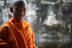 Khmer Smile: Bayon:  (mboogiedown) Tags: world travel light boy shadow orange heritage smile face stone asian temple hope interestingness ancient asia cambodia king peace cambodian khmer bokeh nirvana robe buddhist south faith religion culture belief monk carving east holy explore siem reap sacred thom grin 17 southeast tradition angkor wat enlightenment buddah hinduism  unforgettable mystic vii cultural enigmatic monastic saffron indochine sangha bayon robes indochina sacredplaces novice  bhikku  kampuchea   catchycolorsblog mapcambodia    avalokitesvara cambogia theravada interestingness30 i500 travelforpeace bokehphotooftheday gtaggroup goddaym1 reab samnang asamazingasangkorwatisitpalesincomparisontothebeautyandresilienceofthecambodianpeople 83106 jayavaraman buddhisn camboge kmersmile    bokehsoniceseptember bokehsoniceseptember1 soksabay spiritualsxperience beatravelernotatourist itsallaboutthepeople reasontolearnkhmer soksabaychete dontjustseetheworldexperienceit placestoseebeforeyoudie peopleiwillneverforget experiencecambodia livingfaith ifthephotographerisinterestedinthepeopleinfrontofhislensandifheiscompassionateitsalreadyalottheinstrumentisnotthecamerabutthephotographer~evearnold smilesofthebayon khmersmiles colorsofcambodian interestingness3010806