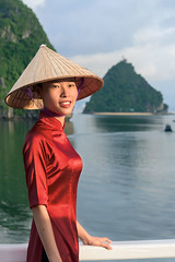 Woman in red (tmeallen) Tags: water smiling vietnam unescoworldheritage halongbay seastacks shipboard cooliehat vietnamesewoman redsilkdress