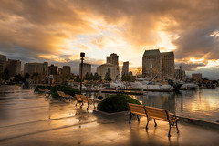Empty Benches (David Colombo Photography) Tags: reflection water skyline clouds sunrise bench landscape boats gold dawn hotel harbor nikon downtown glow skyscrapers sandiego sidewalk hyatt benches d800 wetpavement davidcolombo davidcolombophotography sandiegodowntownsunrise