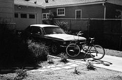 Two Vehicles (bhop) Tags: mustang bicycle vintagecar vintage car musclecar ford beachcruiser los angeles california bw black white blackandwhite monochrome kodak trix 400tx rollei 35 se 35se film filmcamera filmshooter diy v700 40mm block party