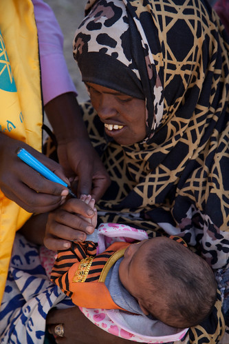 Kos Tahir holds her 40 day old daughter Fatuma Abshir as her finger is marked indicating that she has received her polio vaccination