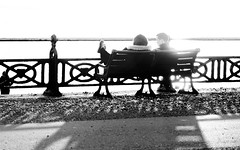 Kicking Back (Fourteenfoottiger) Tags: hove promenade beach seafront seaside brighton fence railings street people candid bench streetphotography highcontrast sunshine sundown mono monochrome blackandwhite backlit