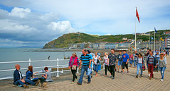 People enjoying the Promenade at Aberystwyth, in the background you can see the new Bandstand. (Minoltakid) Tags: uk summer people dog wales buildings walking fun town ross seaside day westwales sitting unitedkingdom streetphotography oldbuildings flags aberystwyth promenade seafront bandstand ceredigion aber lotsofpeople colourfulbuildings rossevans minoltakid theminoltakid rossdevans