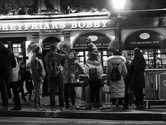 the pub, the dog and the tourists (byronv2) Tags: edinburgh edimbourg scotland edinburghbynight night nuit nacht oldtown winter street candid peoplewatching greyfriars greyfriarsbobby pub bar inn history dog statue chien georgeivbridge candlemakerrow blackandwhite blackwhite bw monochrome