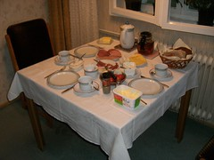 Supper at My Mom's Place (traveling peter) Tags: food brown white fish berlin cup yellow wall cheese germany bread table carpet evening chair europe basket floor tea curtain leg knife margarine plate fork spoon 2006 ham september sugar livingroom pot indoo