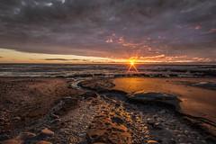 Brooding (zebedee1971) Tags: landscape sea beach river stream water ocean sand coastal coast sun light sunlight sunset dusk moody dark rocks rocky stones cloud sky orange bright rays