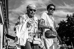 Street - Age (François Escriva) Tags: street streetphotography candid people olympus omd paris france black white bw noir blanc nb sky clouds sun light blue green buildings trees women mother daughter sunglasses age years aged elder walking
